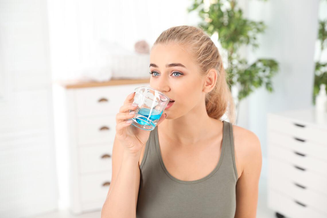 chica enjuagando boca clorhexidina